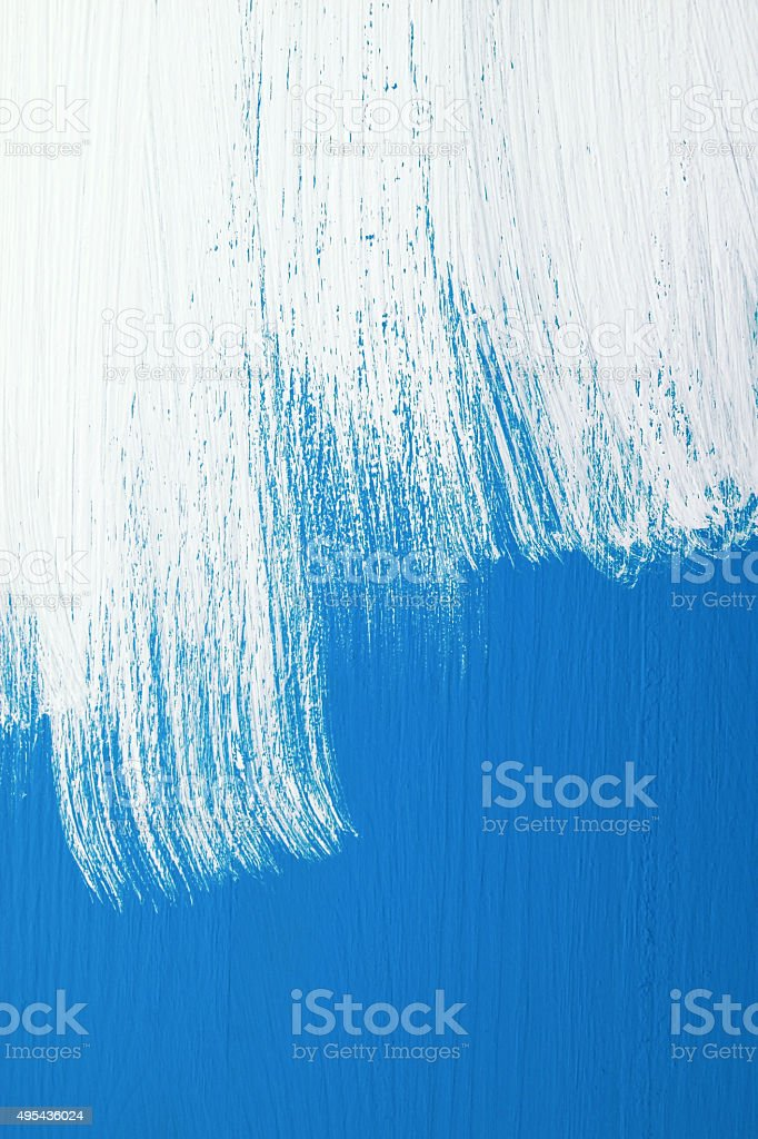 Blue board being roughly painted with white paint stock photo
