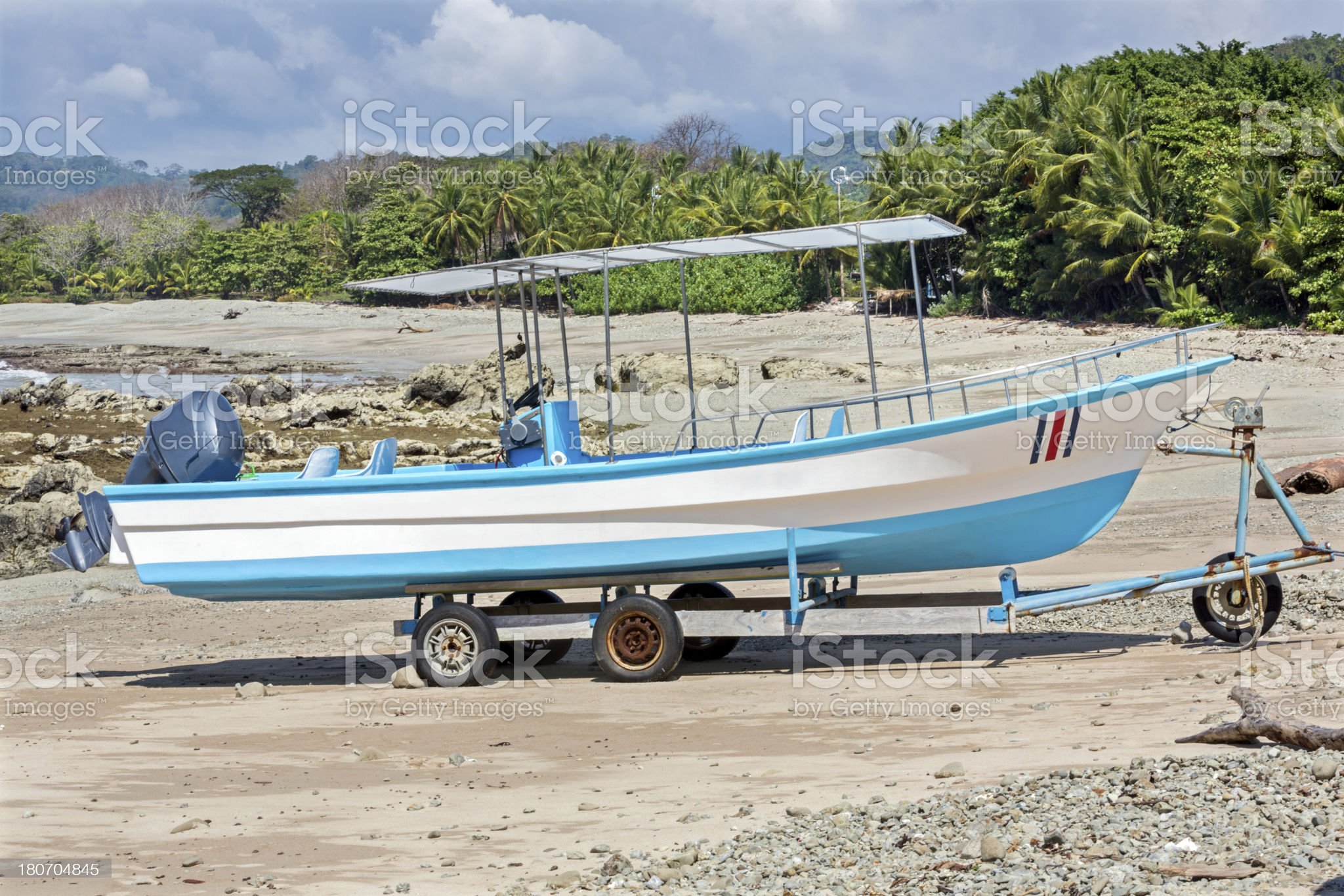 blue boat trailered on white sand beach royalty-free stock photo