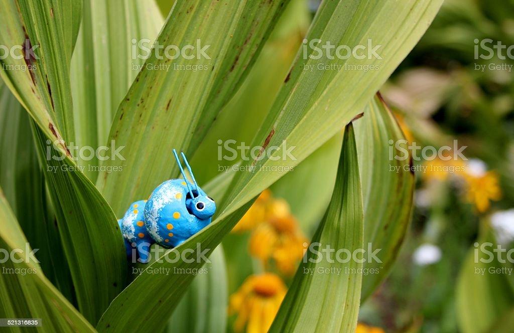 Blue bobble head caterpillar peeking out of skunk cabbage stock photo