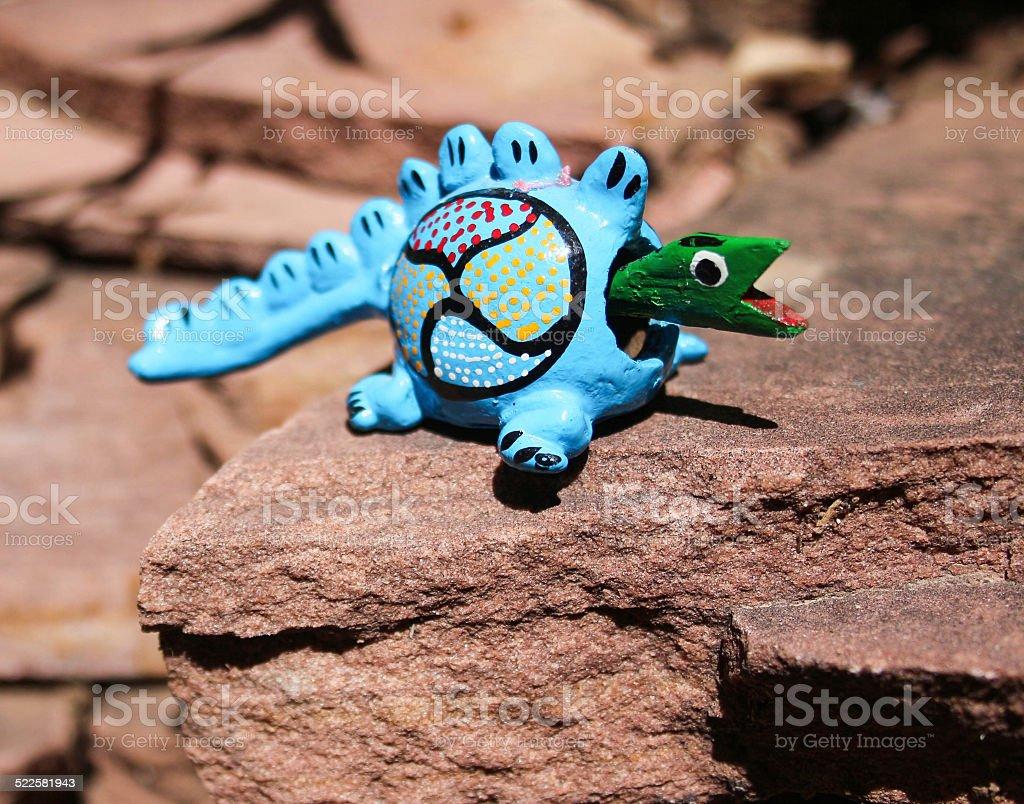 Blue bobblehead toy reptile on flagstone stock photo