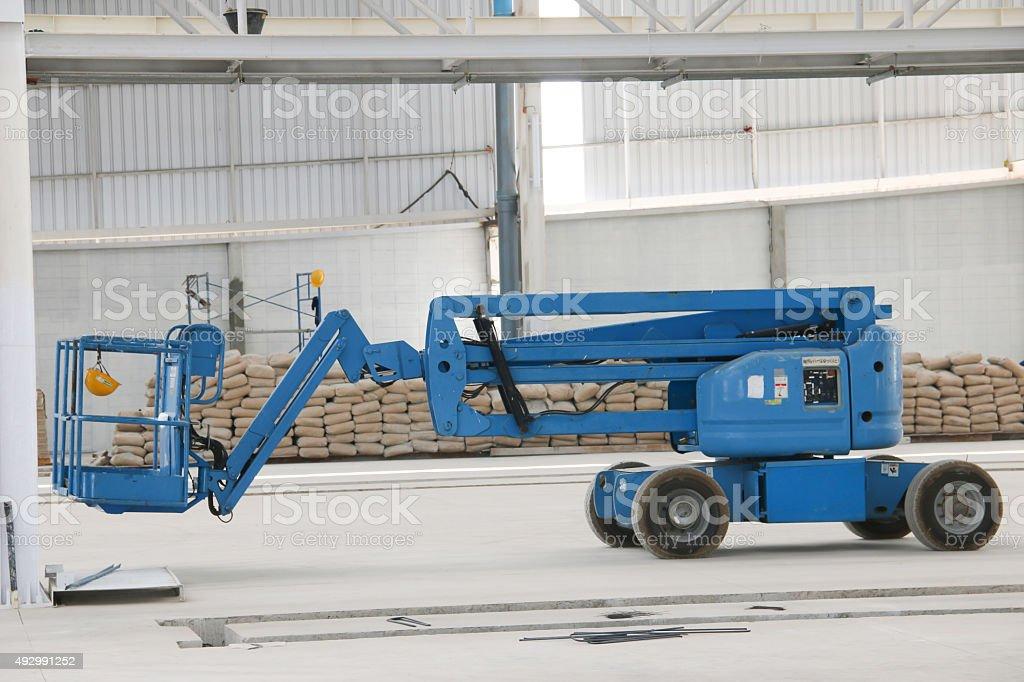 blue boom lift indoor stock photo