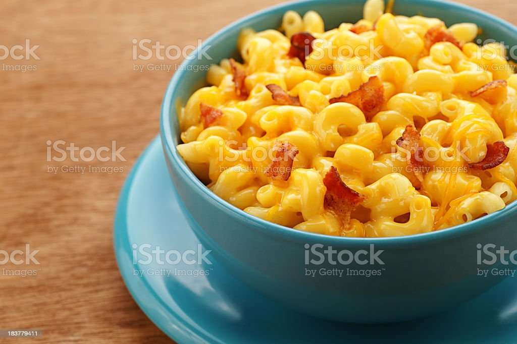 A blue bowl of macaroni and cheese with bacon pieces stock photo