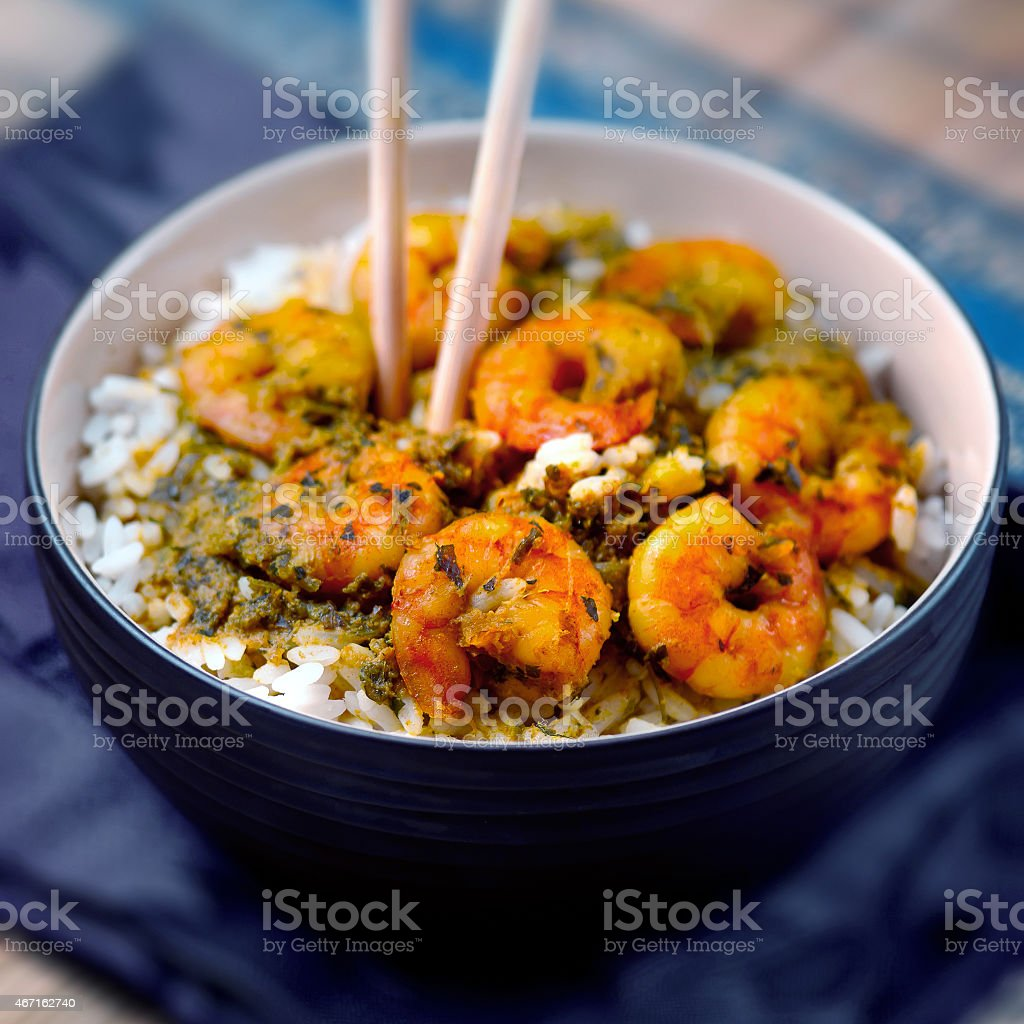 Blue bowl of rice, shrimp and seasonings with chop sticks stock photo
