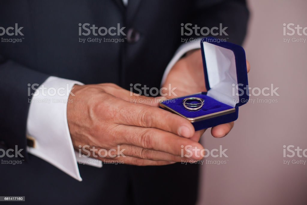 blue box with a ring in a man's hand, the bride holding a box with rings stock photo