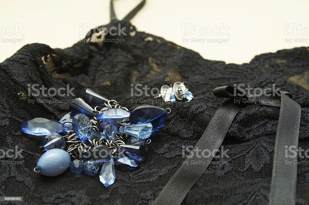 Blue bracelet and earrings lying on black lingerie. royalty-free stock photo