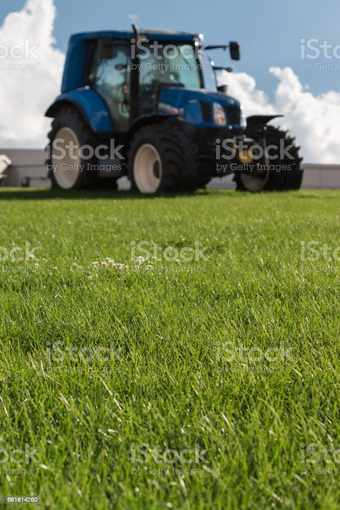 Blue Brilliant Agricultural Tractor on Green Declivity Field stock photo