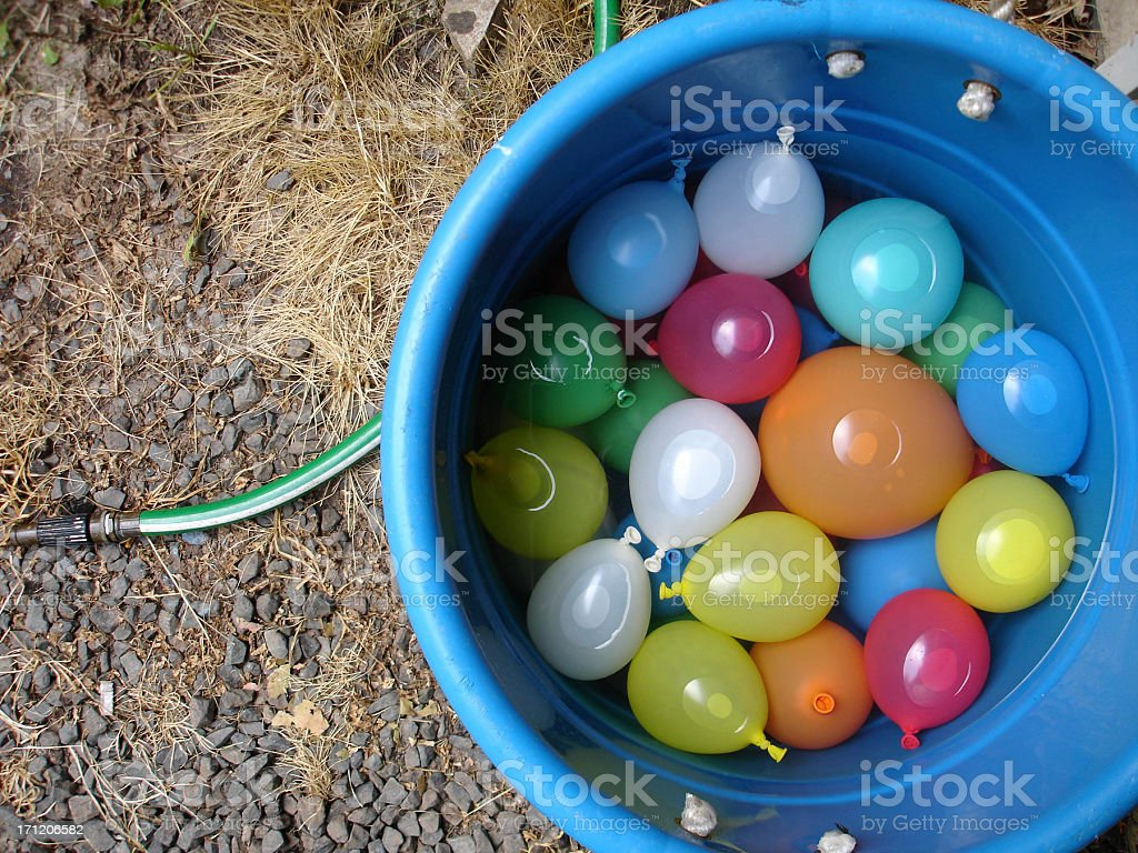 A blue bucket of filled water balloons on a gravel surface stock photo