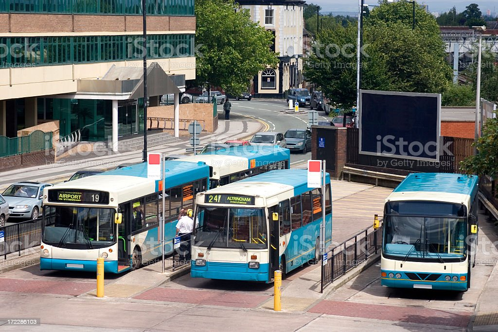Blue buses waiting at a station in a small city stock photo