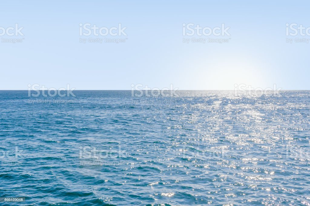 Blue calm sea with sunlight reflected on it stock photo