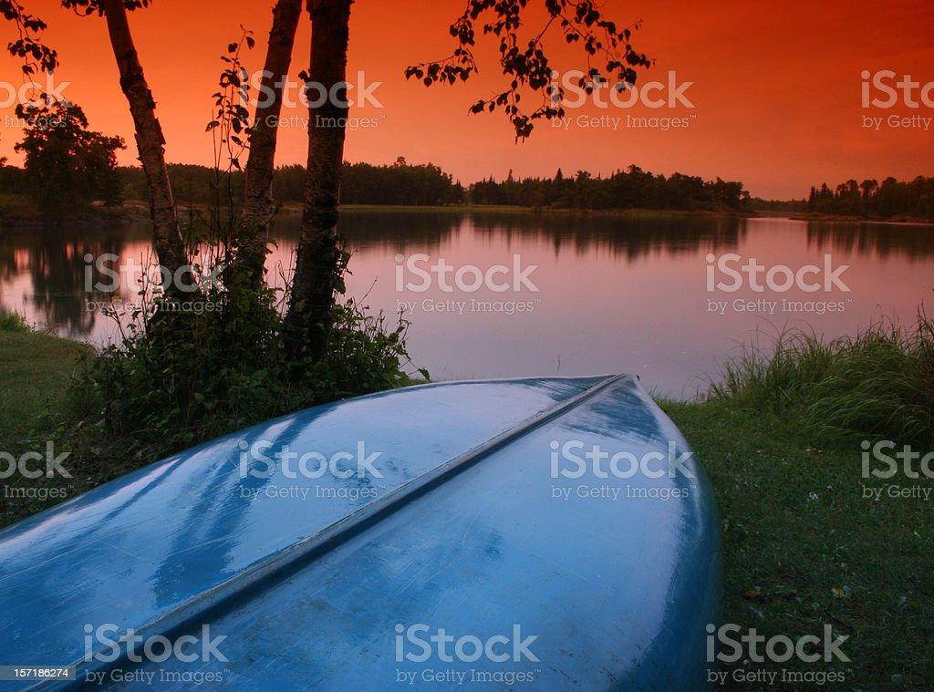 Blue Canoe and Beautiful Sunset on the Lake royalty-free stock photo