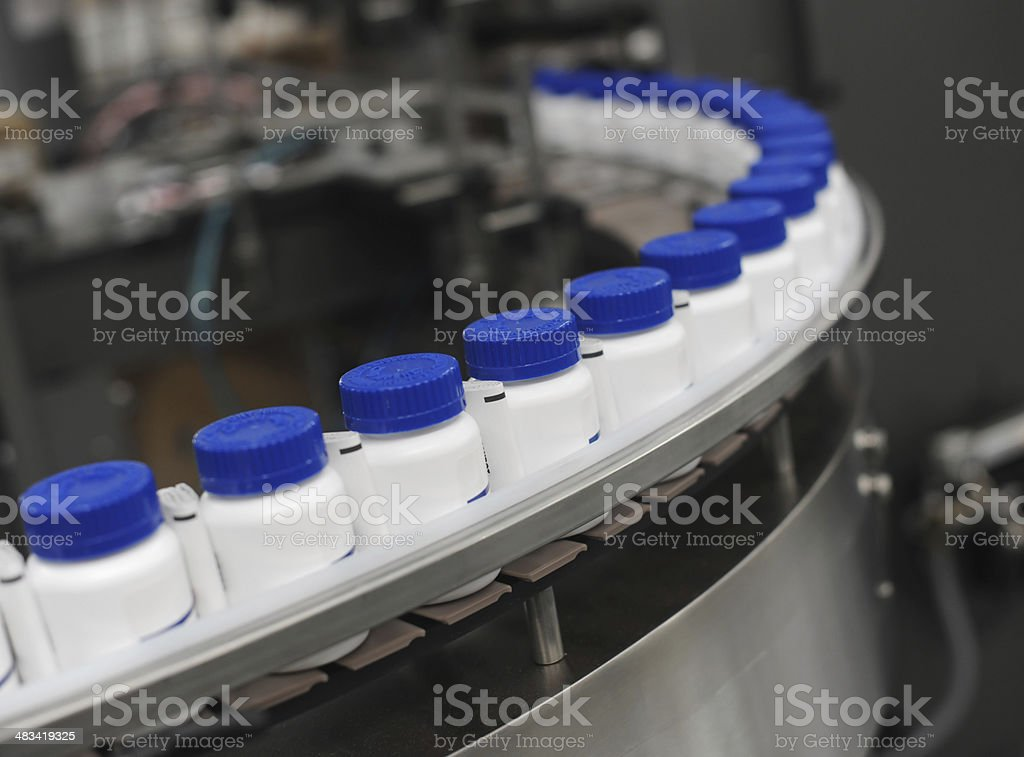 Blue Capped Drug Bottles on Conveyor stock photo