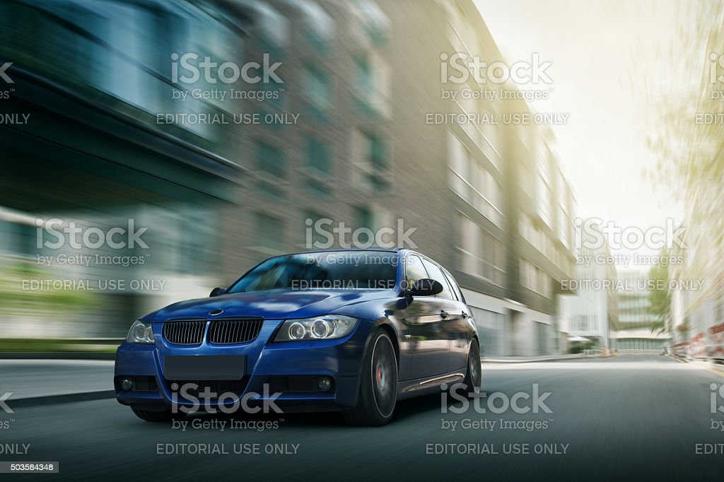 Blue car BMW E90 fast speed drive on city road stock photo