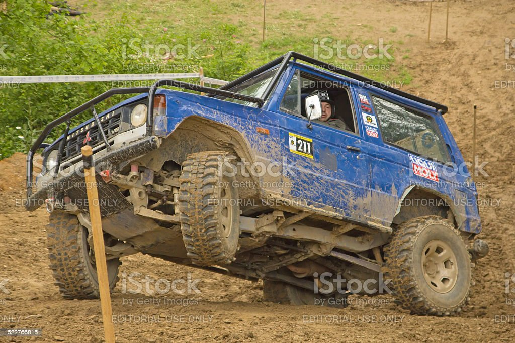 Blue car on a steep slope in the terrain stock photo