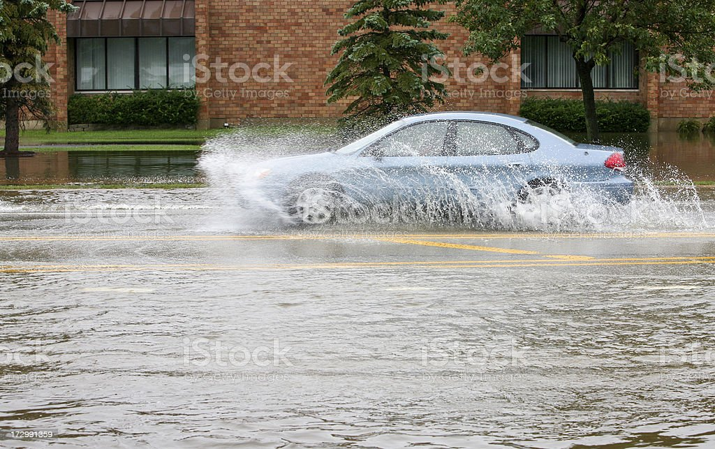 blue car splashes on flooded street royalty-free stock photo