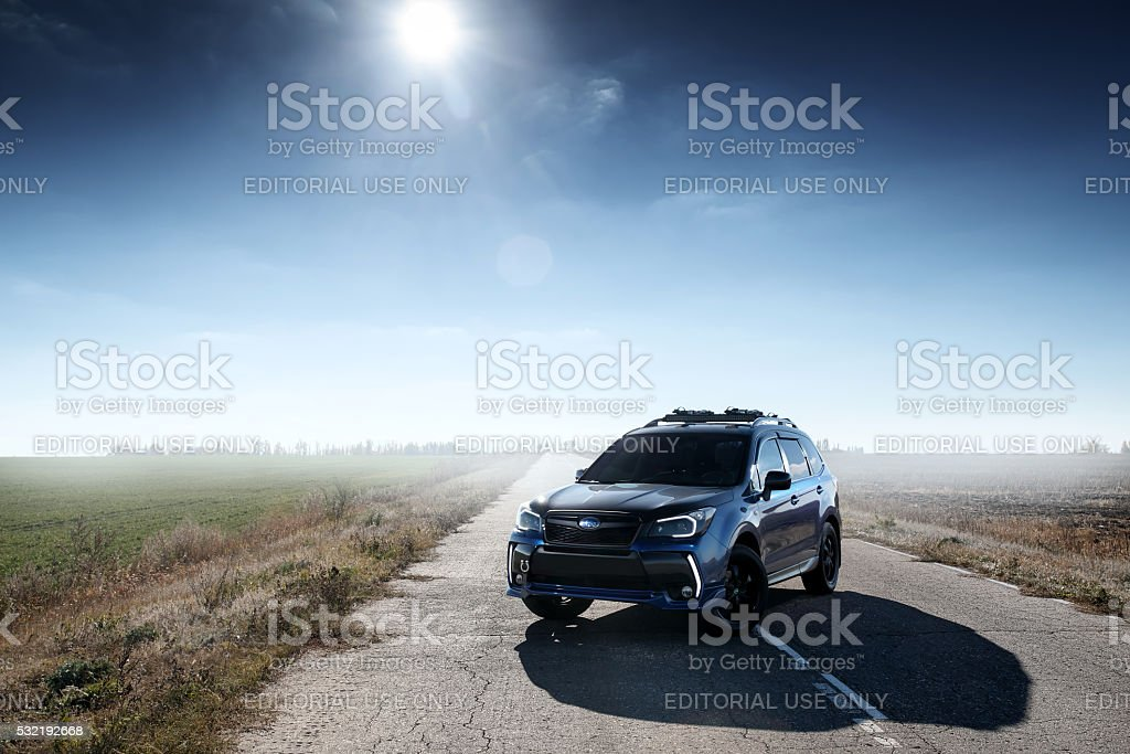 Blue car Subaru Forester standing on asphalt road at daytime stock photo