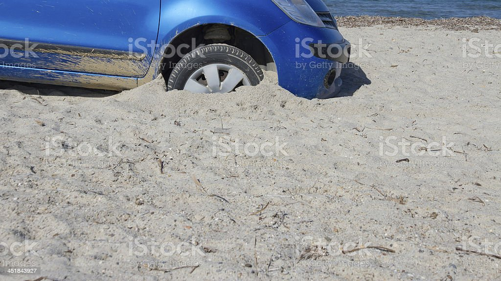 Blue car with front tired trapped in sand on the beach stock photo