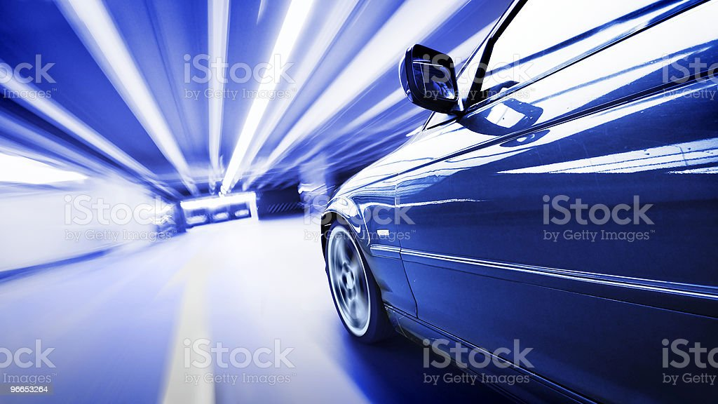 Blue car zooming through a road tunnel stock photo