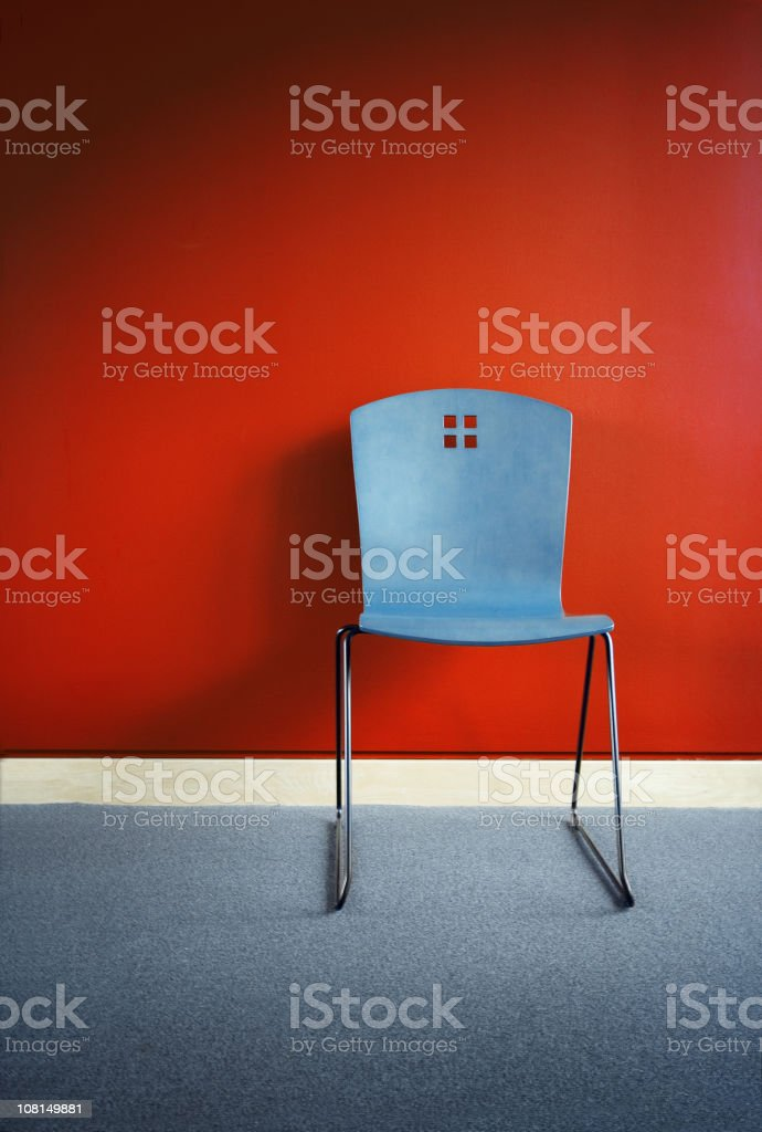 Blue Chair Against Red Wall royalty-free stock photo