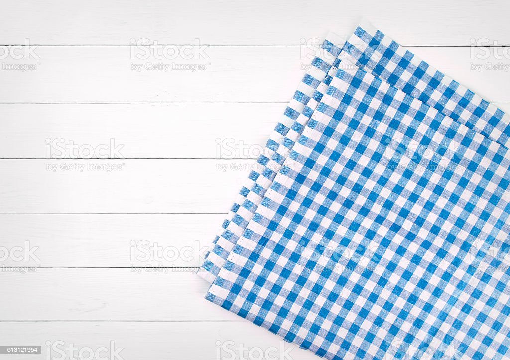 Table Top View blue checkered folded tablecloth on white wooden table top view