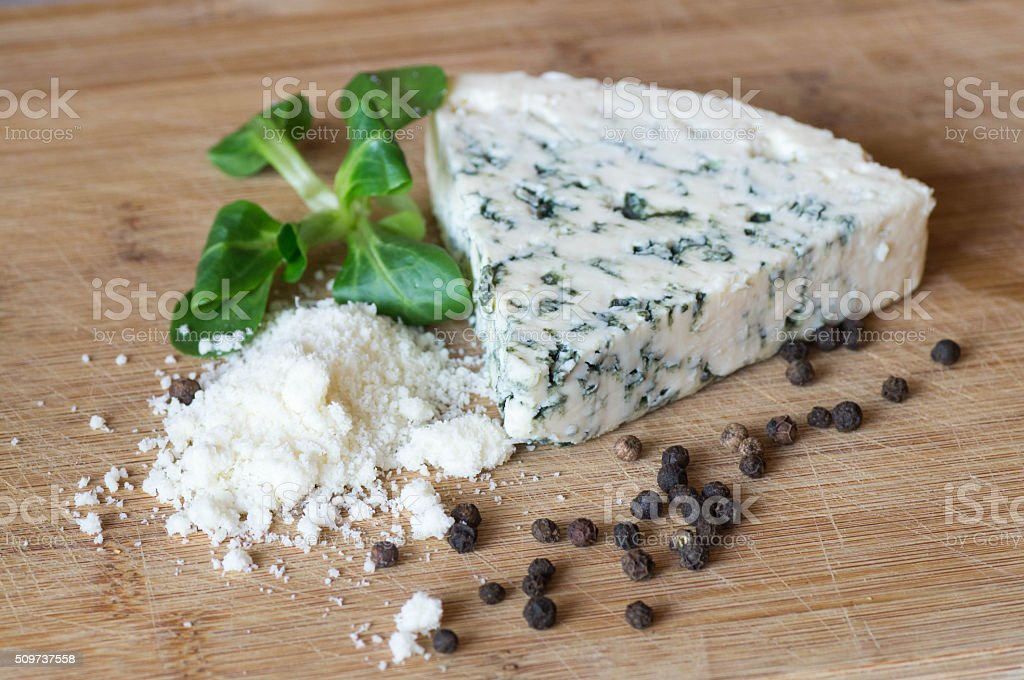 Blue cheese and ground parmesan on wooden board stock photo