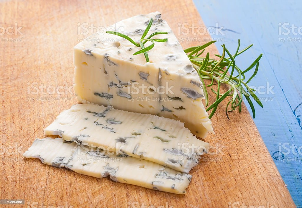 blue cheese with a sprig of rosemary stock photo