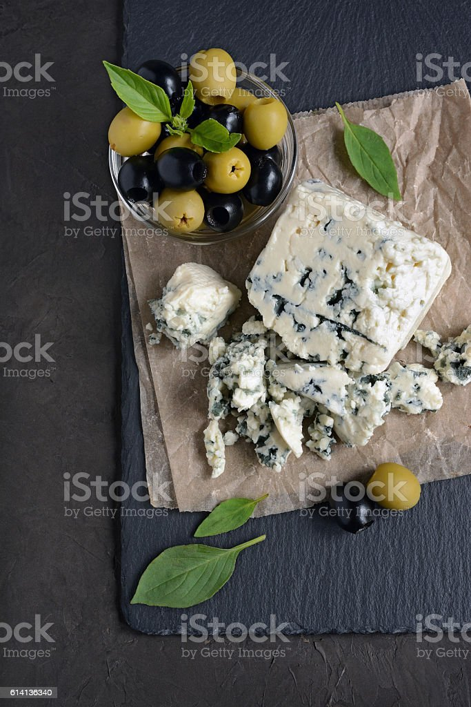 Blue cheese with black and green olive, basil and crispbread stock photo