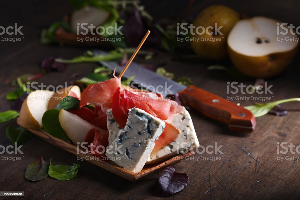 blue cheese with prosciutto and pear on a wooden table stock photo