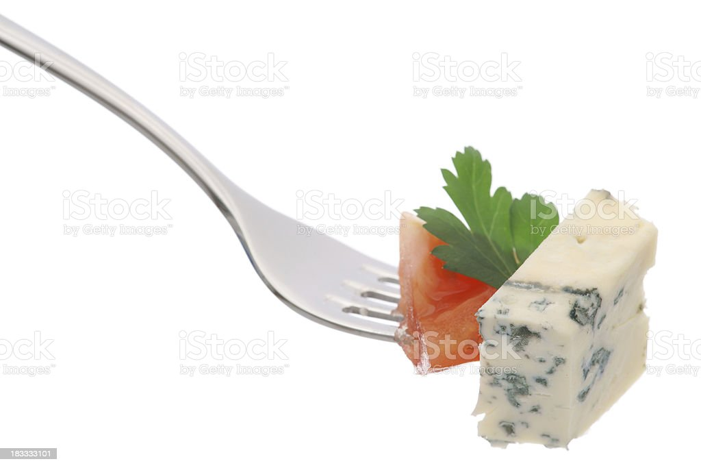 Blue cheese with tomato and parsley on fork isolated stock photo