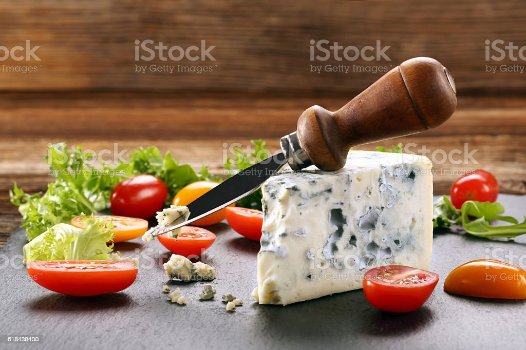 Blue cheese with tomato on stone background stock photo