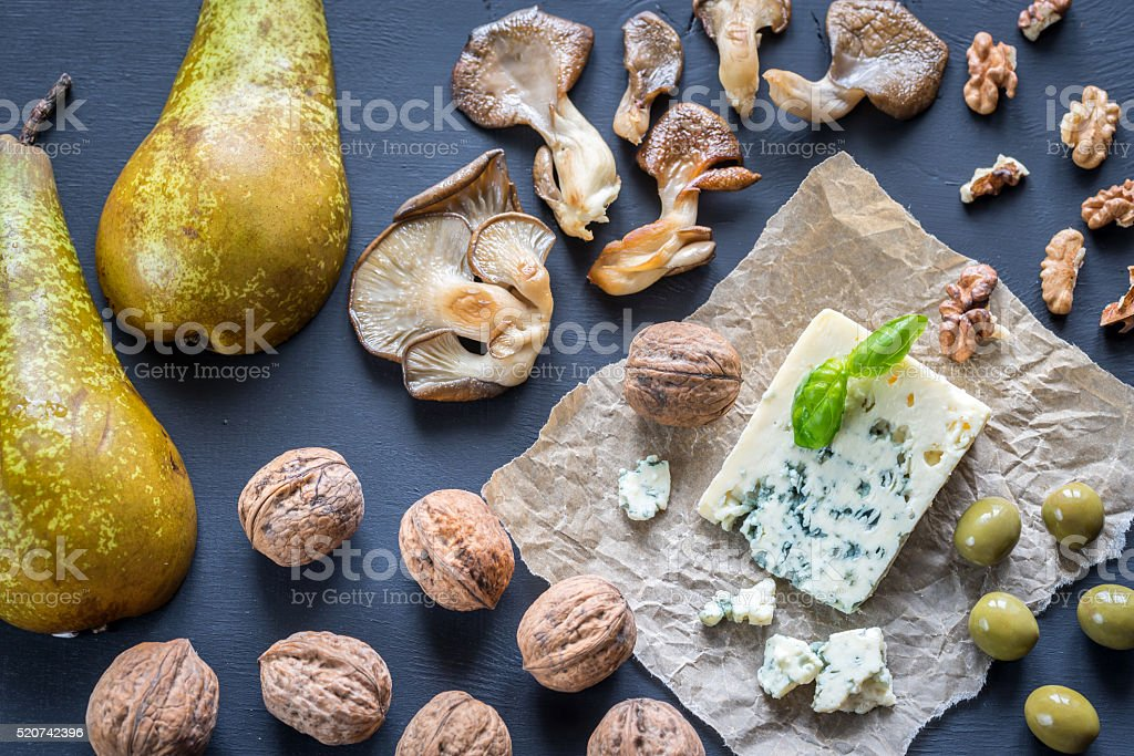 Blue cheese with walnuts, oyster mushrooms and green olives stock photo