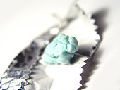 Blue chewed gum on a silver wrapper