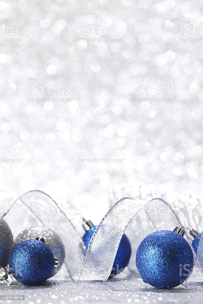 Blue Christmas balls and ribbon on silver sparkle background stock photo