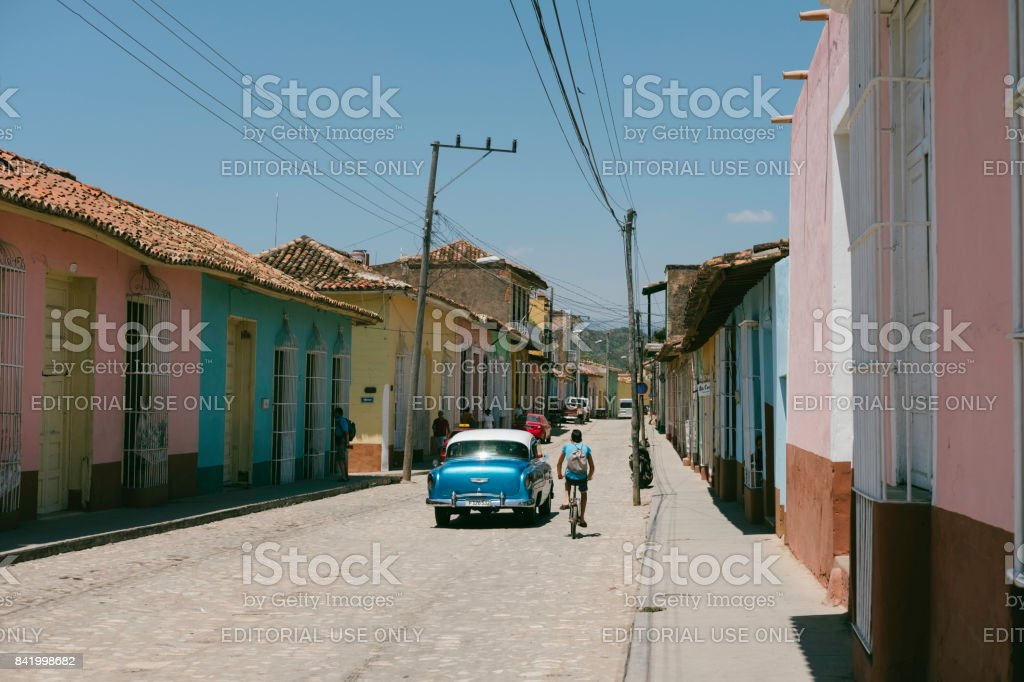 Blue classic car and pedestrians on colorful city streets in Cuba stock photo