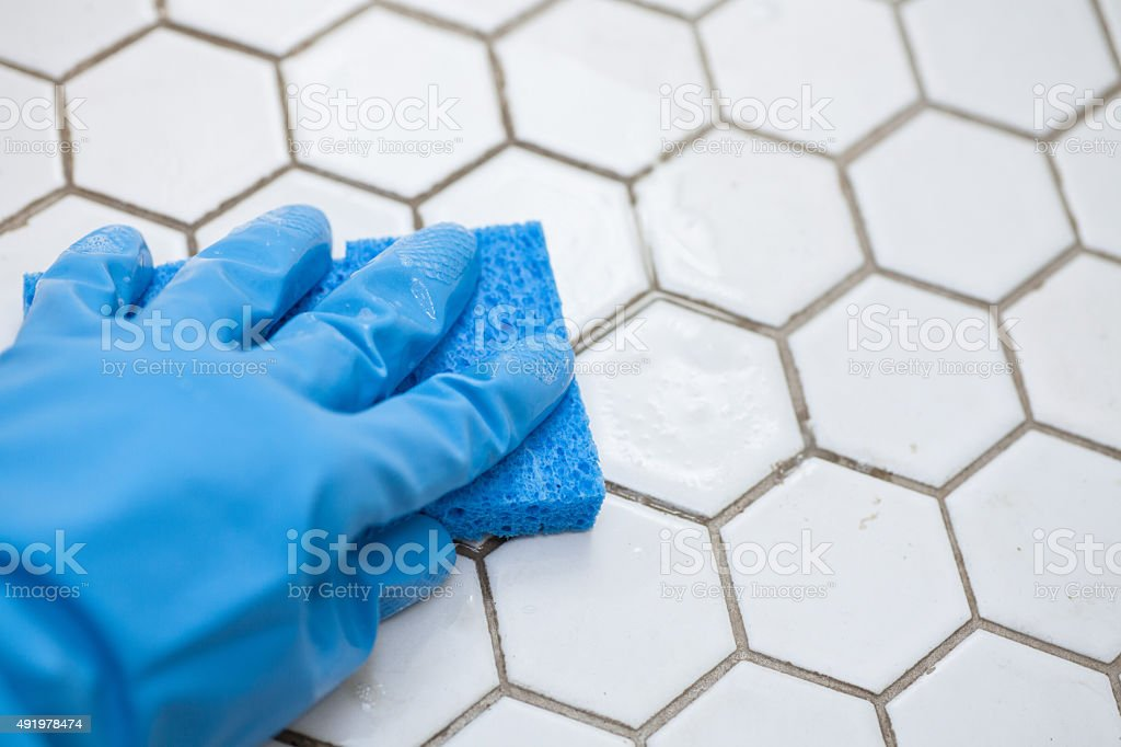 blue cleaning gloves holding a sponge cleaning a tile floor stock photo