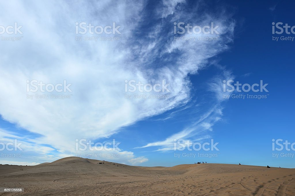 Blue cloudy sky over sand dunes in the evening stock photo
