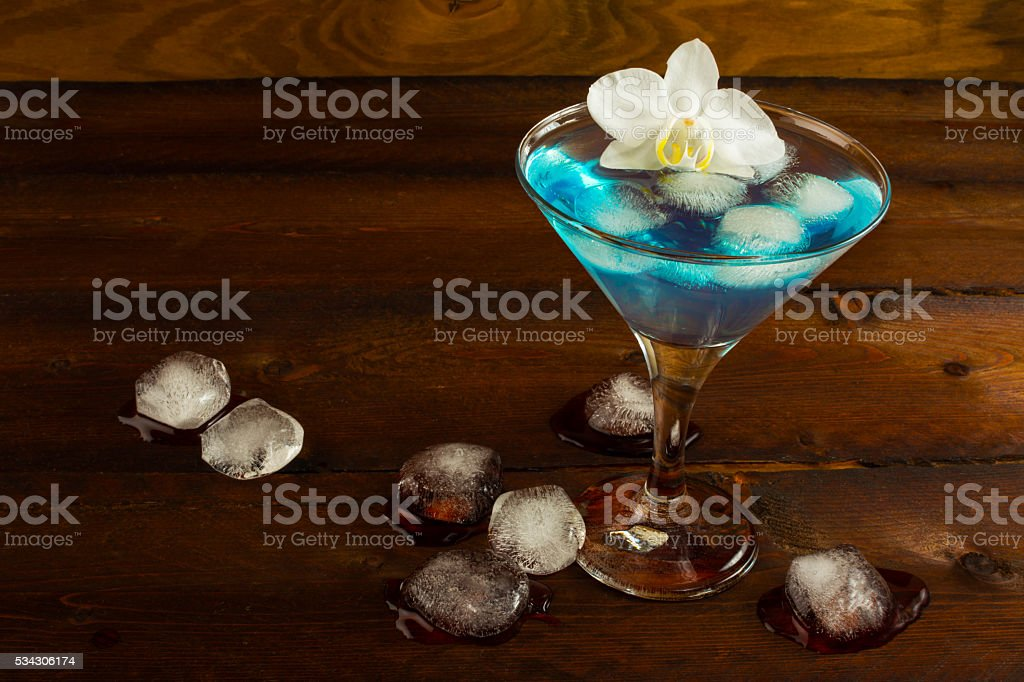 Blue cocktail served with orchid stock photo