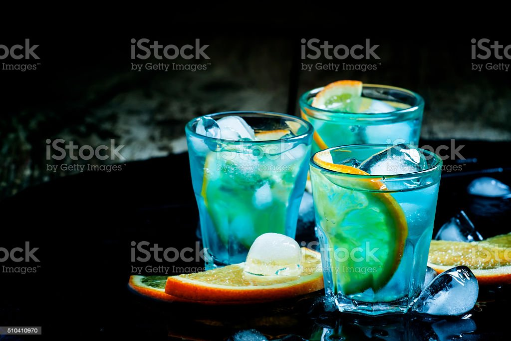 Blue cocktail with ice cubes and slices of orange stock photo