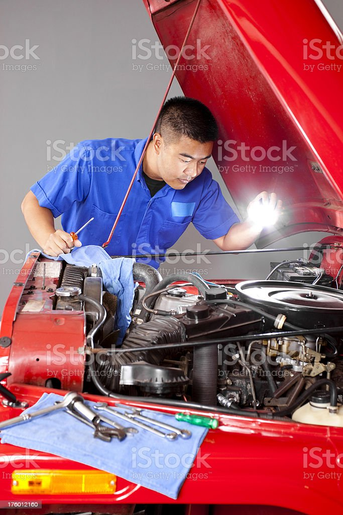 Blue collar Asian mechanic working motor vehicle open hood royalty-free stock photo