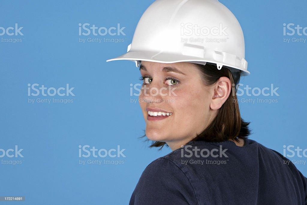 Happy female blue collar worker shot on blue.