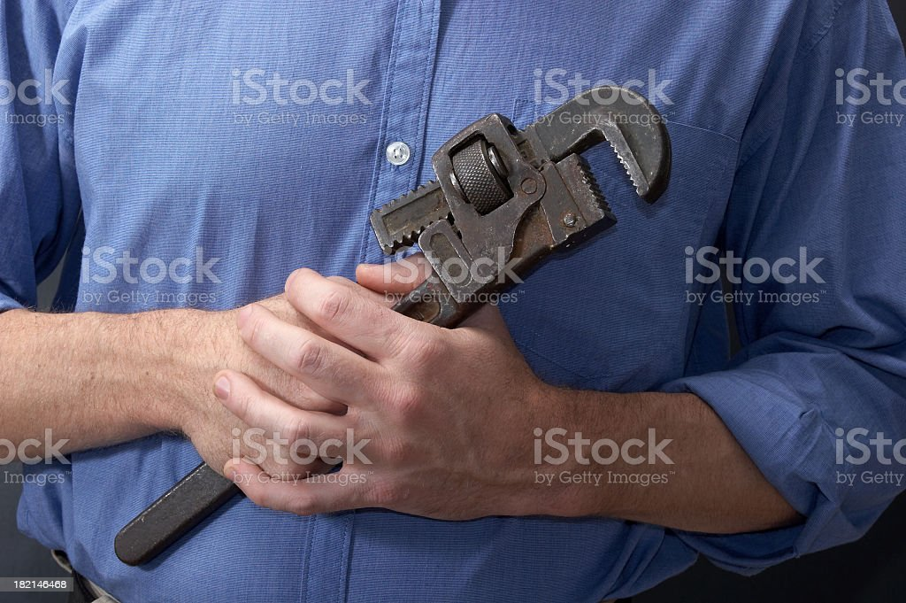 Blue collar plumber holding a wrench with both hands royalty-free stock photo