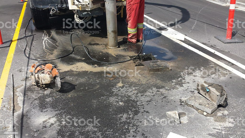 Blue collar worker cutting a hole in concrete stock photo