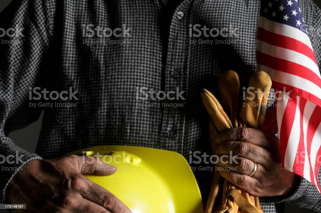 Blue collar worker holding American flag and hard hat royalty-free stock photo