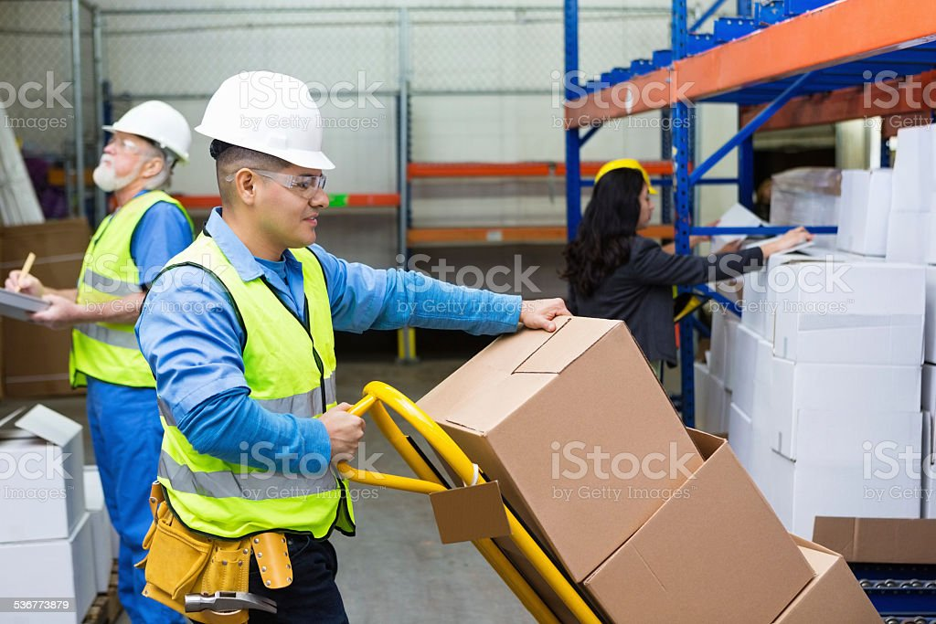 Blue collar workers in warehouse moving boxes before shipping stock photo