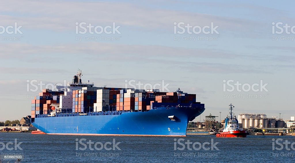 Blue containership with containers being tugged in the Rotterdam harbour stock photo