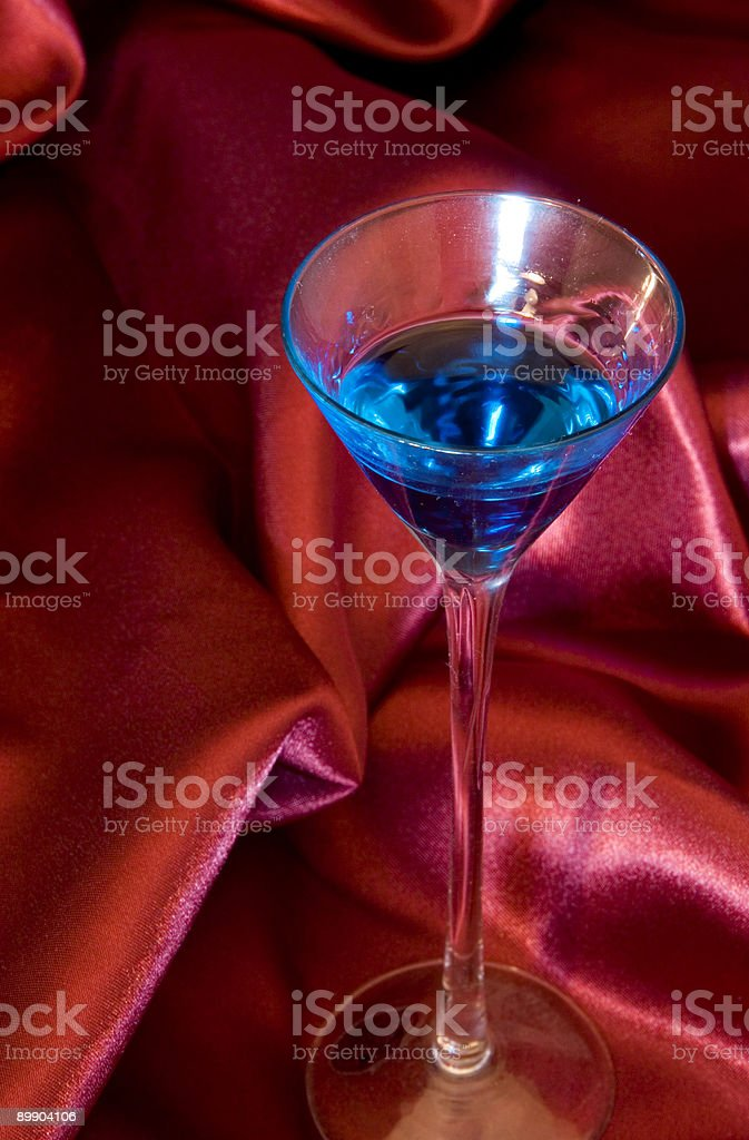 Blue Cordial Glass on Red Satin stock photo
