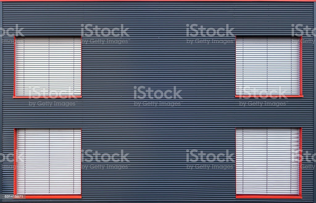 Blue corrugated iron facade with four closed windows royalty-free stock photo