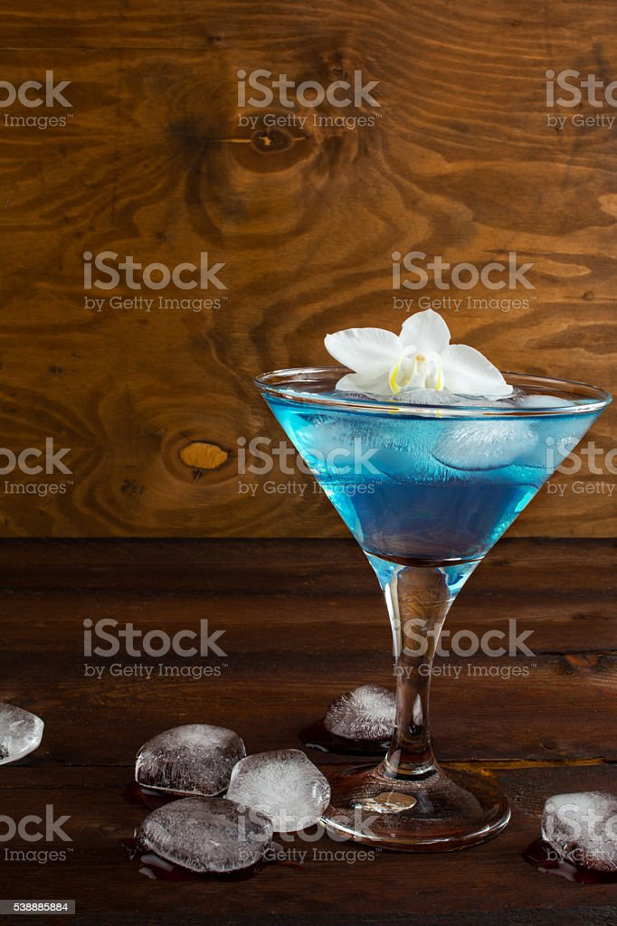 Blue cosmopolitan cocktail on wooden background stock photo