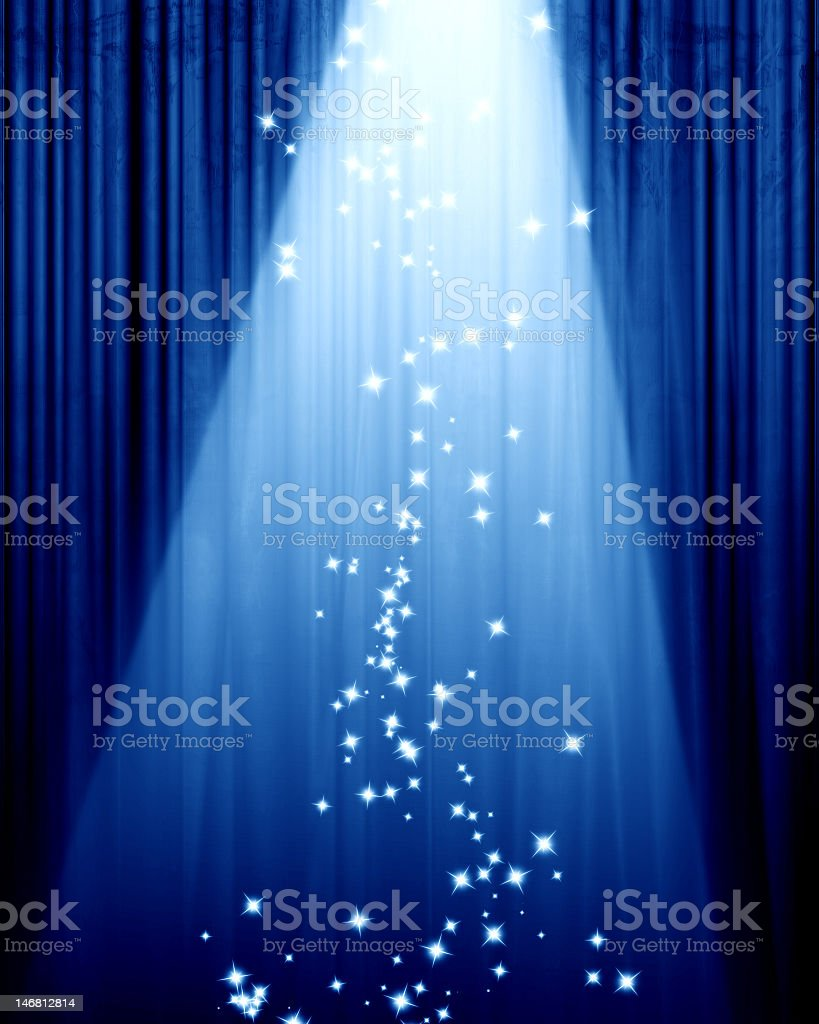 Blue curtain in a theater and a spotlight with sparkles stock photo