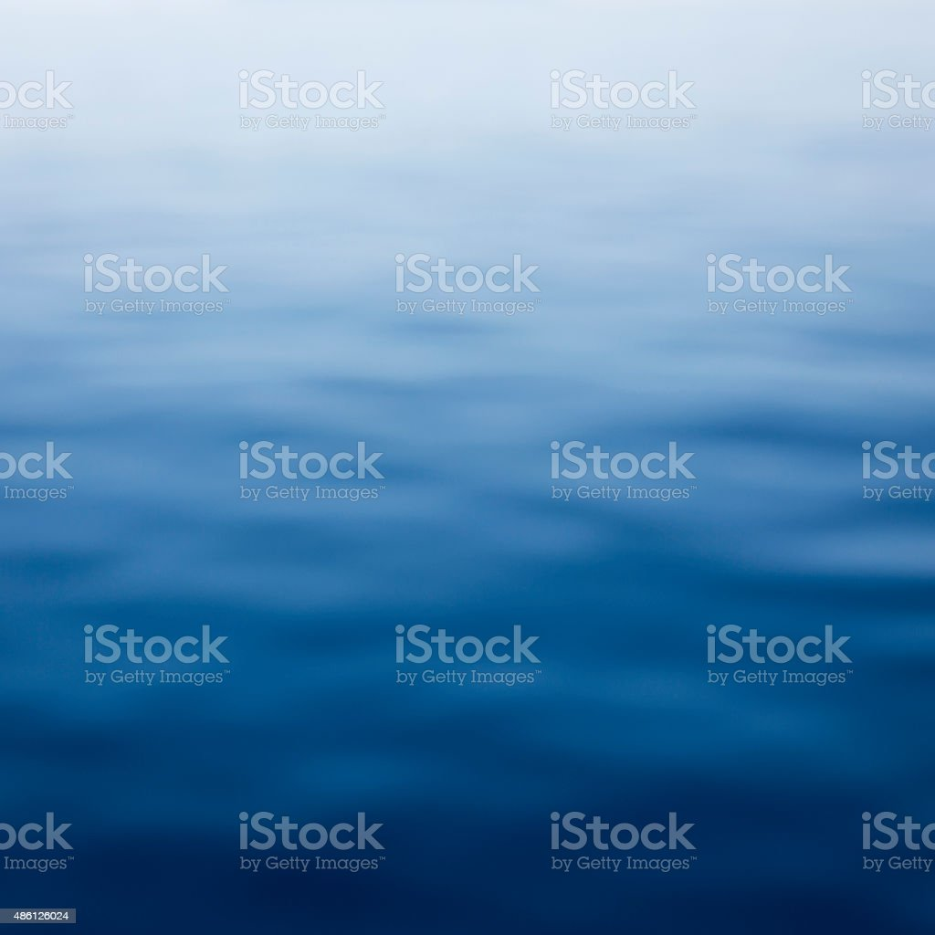 Blue defocused sea background with blurry waves stock photo