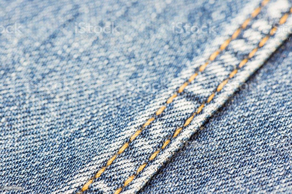 Blue denim with yellow stitching. stock photo